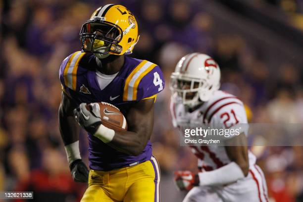 Alfred Blue of the Louisiana State University Tigers runs for a touchdown past Arius Wright of the Western Kentucky Hilltoppers at Tiger Stadium on...