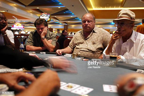 Alfred Bryant Dave Bee Stephen Madel and H Barzilay play a game of poker May 11 2004 during the grand opening for the Seminole Hard Rock Hotel and...