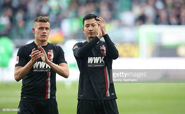 Alfred Finnbogason and DongWon Ji of Augsburg applaud the fans after the Bundesliga match between VfL Wolfsburg and FC Augsburg at Volkswagen Arena...