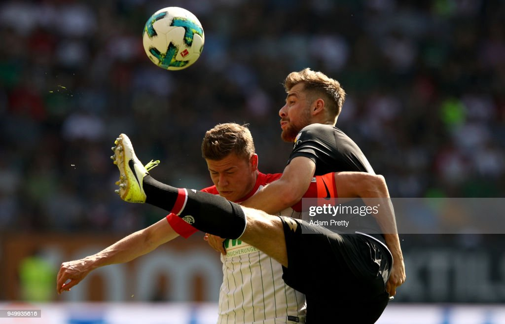Alfred Finnbogason (L) of Augsburg and Alexander Hacker of Mainz battle for the ball during the Bundesliga match between FC Augsburg and 1. FSV Mainz 05 at WWK-Arena on April 22, 2018 in Augsburg, Germany.