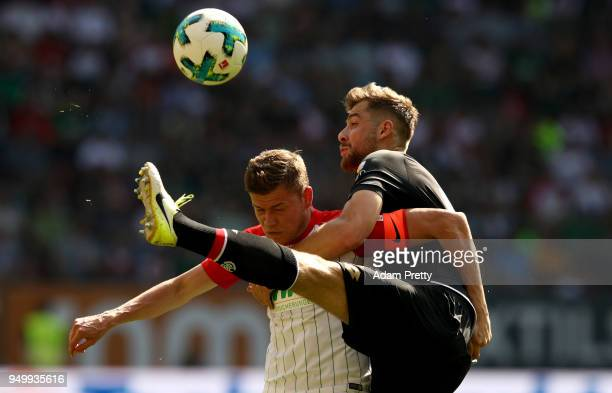 Alfred Finnbogason of Augsburg and Alexander Hacker of Mainz battle for the ball during the Bundesliga match between FC Augsburg and 1 FSV Mainz 05...