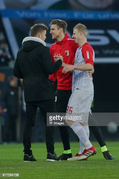 Alfred Finnbogason of Augsburg and Goalkeeper Andreas Luthe of Augsburg congratulate Martin Hinteregger of Augsburg after the Bundesliga match...