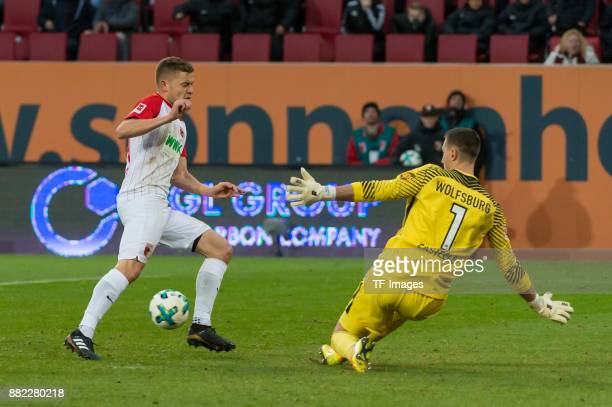 Alfred Finnbogason of Augsburg and Goalkeeper Koen Casteels of Wolfsburg battle for the ball during the Bundesliga match between FC Augsburg and VfL...