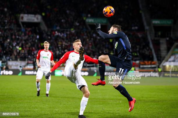 Alfred Finnbogason of Augsburg and Matthew Leckie of Hertha Berlin battle for the ball during the Bundesliga match between FC Augsburg and Hertha BSC...