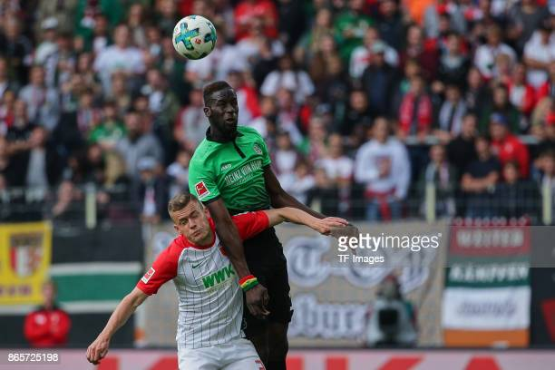 Alfred Finnbogason of Augsburg and Salif Sane of Hannover battle for the ball during the Bundesliga match between FC Augsburg and Hannover 96 at...
