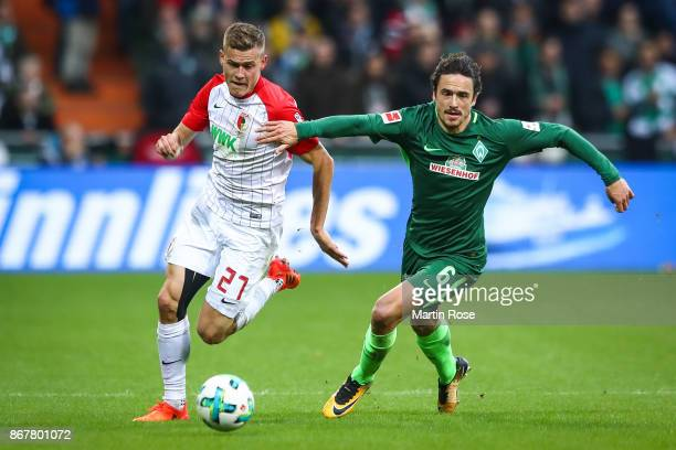 Alfred Finnbogason of Augsburg and Thomas Delaney of Bremen battle for the ball during the Bundesliga match between SV Werder Bremen and FC Augsburg...