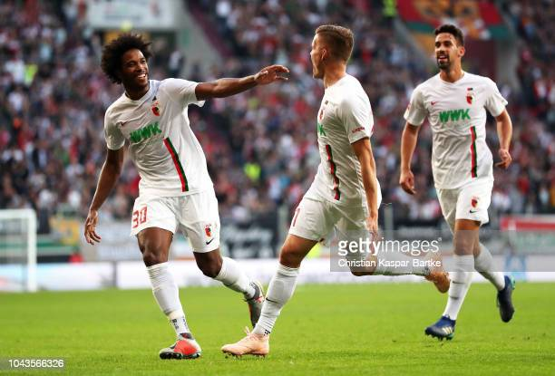 Alfred Finnbogason of Augsburg celebrates with Caiuby of Augsburg after Alfreo Finnbogason scored their team's second goal during the Bundesliga...