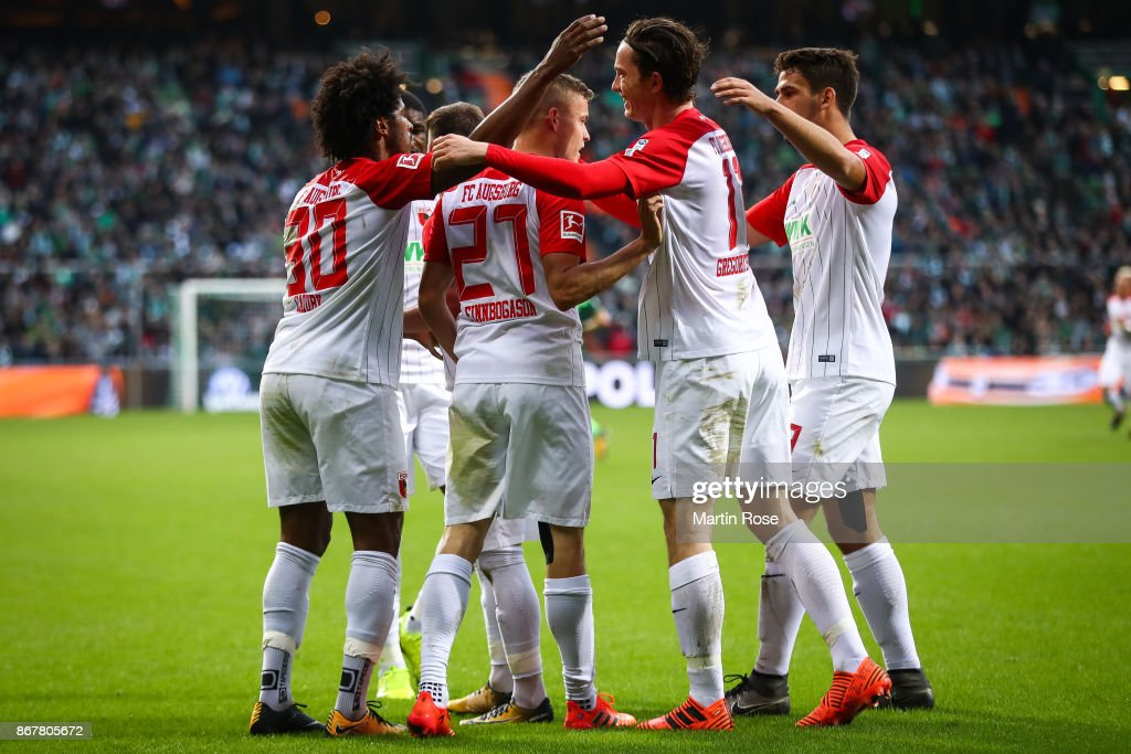 Alfred Finnbogason #27 of Augsburg celebrates with his team-mates after scoring his team's second goal after penalty shot to make it 0-2 during the Bundesliga match between SV Werder Bremen and FC Augsburg at Weserstadion on October 29, 2017 in Bremen, Germany.