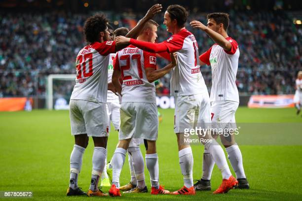 Alfred Finnbogason of Augsburg celebrates with his teammates after scoring his team's second goal after penalty shot to make it 02 during the...