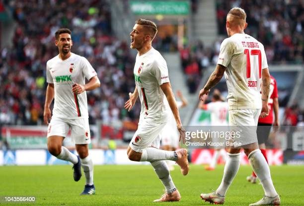 Alfred Finnbogason of Augsburg celebrates with team mates after scoring his team's second goal during the Bundesliga match between FC Augsburg and...