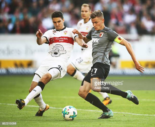 Alfred Finnbogason of Augsburg is challenged by Marcin Kaminski of VfB Stuttgart during the Bundesliga match between VfB Stuttgart and FC Augsburg at...