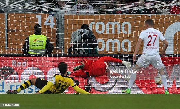 Alfred Finnbogason of Augsburg scores a goal against goalkeeper Roman Buerki and Mats Hummels of Dortmung during the Bundesliga match between FC...