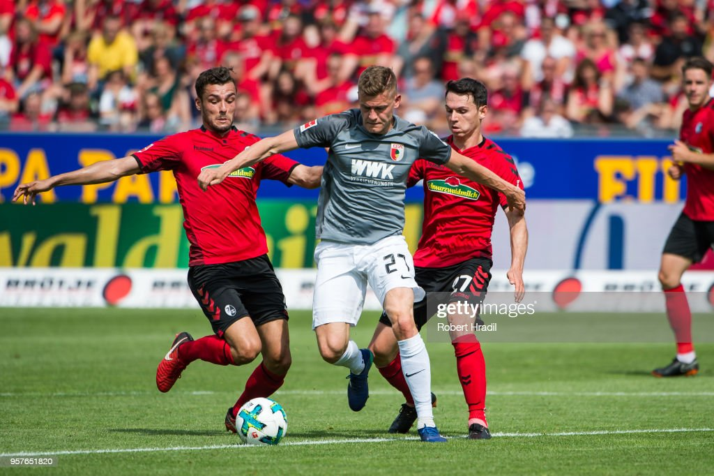 #27 Alfred Finnbogason of Augsburg vies with #5 Manuel Gulde (left) and #17 Lukas Kuebler of Freiburg (right) during the Bundesliga match between Sport-Club Freiburg and FC Augsburg at Schwarzwald-Stadion on May 12, 2018 in Freiburg im Breisgau, Germany.