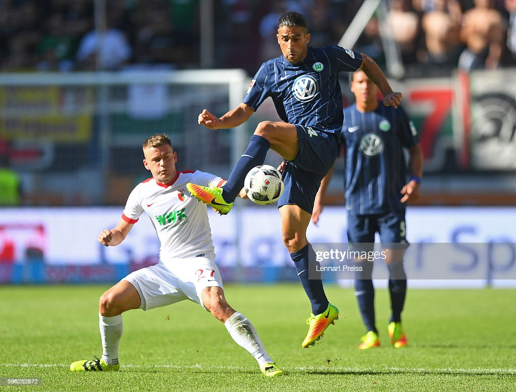 Alfred Finnbogason (L) of FC Augsburg challenges Ricardo Rodriguez of VfL Wolfsburg during the Bundesliga match between FC Augsburg and VfL Wolfsburg at WWK Arena on August 27, 2016 in Augsburg, Germany.