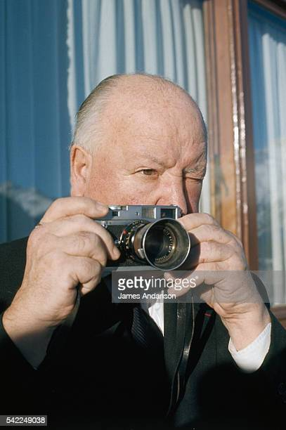 Alfred Hitchcock holding a Leica camera.