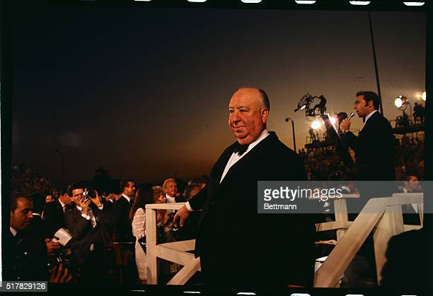 Alfred Hitchcock is shown waving to crowd as he arrives at the Academy Awards presentations