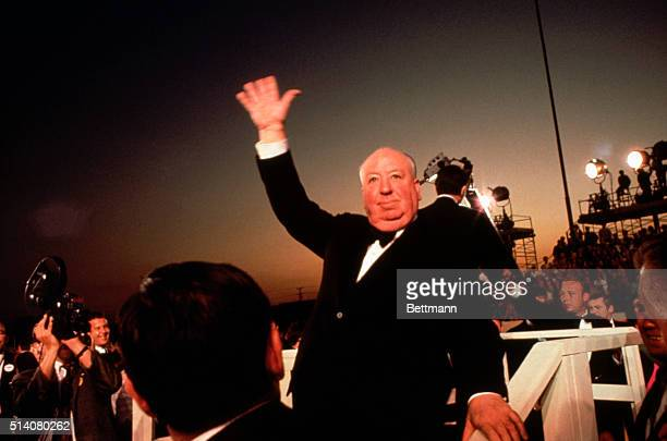 Alfred Hitchcock waves to the crowds upon his arrival at the Academy Awards Ceremony of 1968.