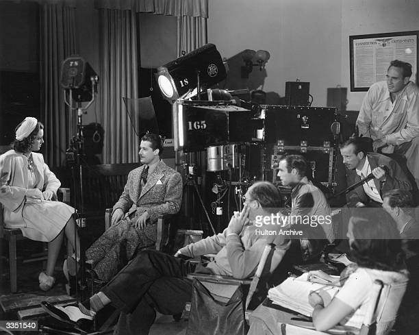Alfred L Werker directs Arleen Whelan and Don Ameche in a rehearsal of the 20th Century Fox film 'Gateway' watched by cameraman Edward Cronjager
