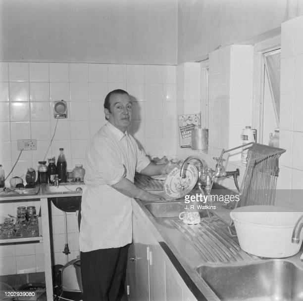 Alfred Lennon , father of John Lennon of The Beatles, washes up dishes in a kitchen in England on 2nd July 1965.