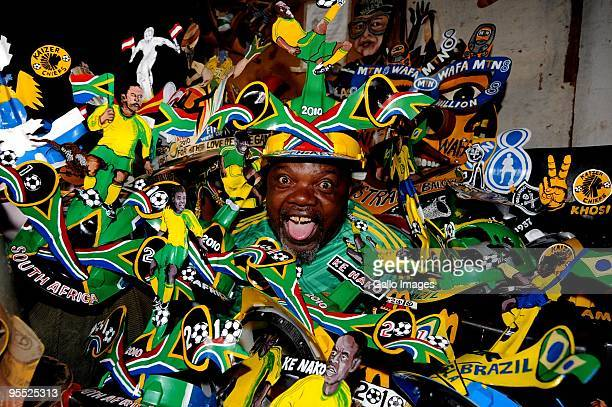 Alfred 'Lux' Baloyi designer of the famous Makarapa football 2010 helmet poses alongside his different designs on January 1 2010 in Germiston South...
