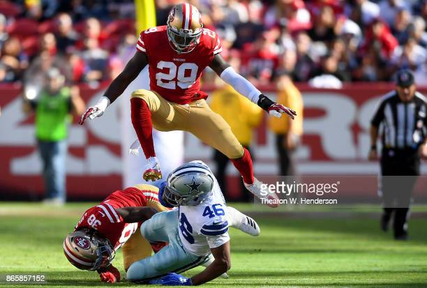 Alfred Morris of the Dallas Cowboys carries the ball and gets tackled by Adrian Colbert of the San Francisco 49ers while Jaquiski Tartt leaps over...