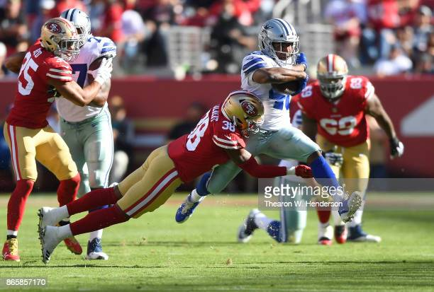 Alfred Morris of the Dallas Cowboys carries the ball and gets tackled by Adrian Colbert of the San Francisco 49ers during an NFL football game at...