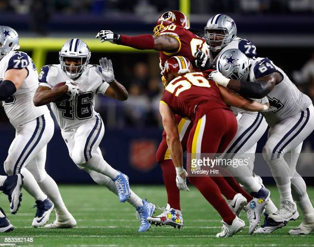 Alfred Morris of the Dallas Cowboys tries to evade Ziggy Hood of the Washington Redskins and Zach Vigil of the Washington Redskins on a carry in the...