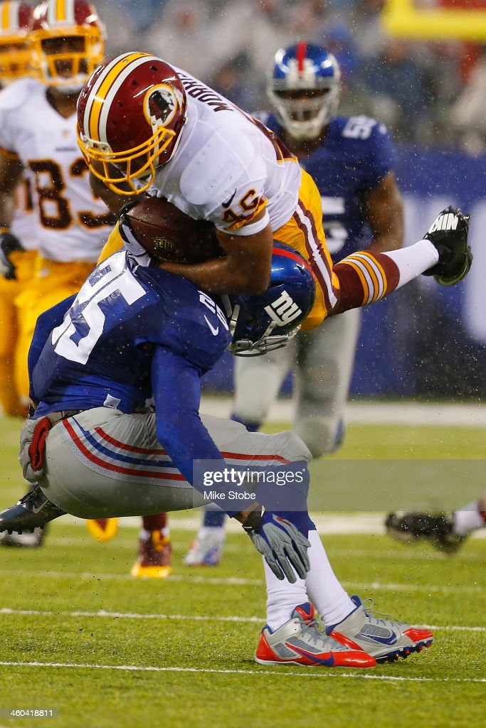 Alfred Morris #46 of the Washington Redskins is tackled by Will Hill #25 of the New York Giants at MetLife Stadium on December 29, 2013 in East Rutherford, New Jersey. Giants defeated the Redskins 20-6.