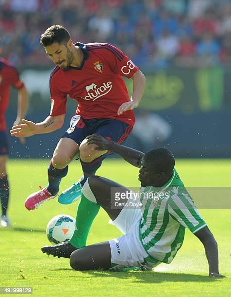 Alfred N'Diaye of Real Betis Balompie tackles Alvaro Cejudo of CA Osasuna during the La Liga match between CA Osasuna and Real Betis Balompie at...