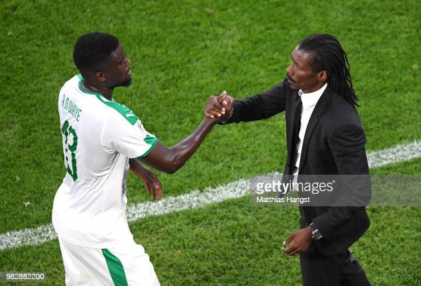 Alfred Ndiaye shakes hands with Aliou Cisse Head coach of Senegal after being substituted during the 2018 FIFA World Cup Russia group H match between...