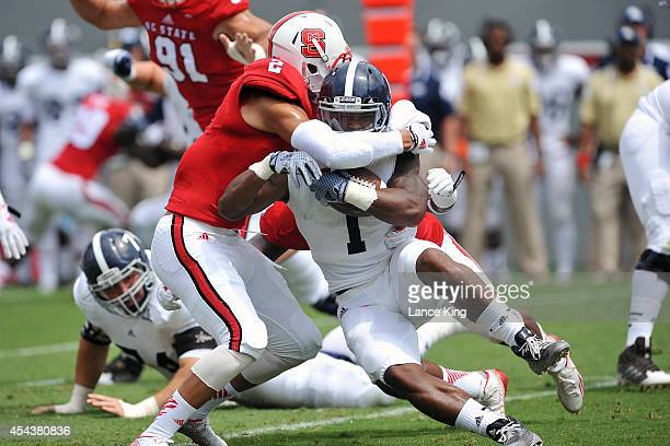 Alfred Ramsby of the Georgia Southern Eagles is tackled by Josh Jones of the North Carolina State Wolfpack at CarterFinley Stadium on August 30 2014...