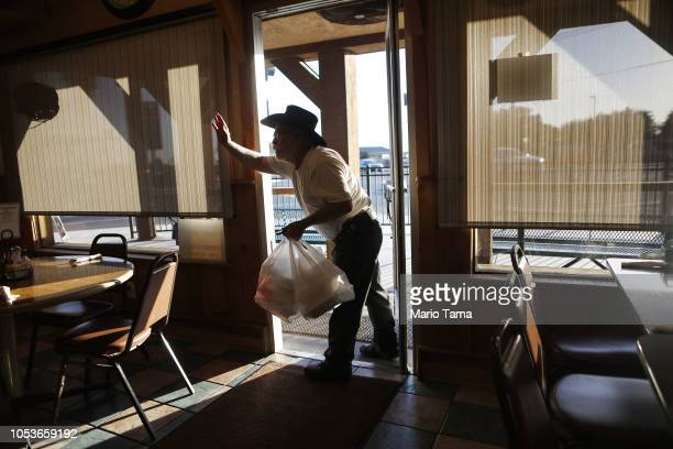 Alfred Sisk waves goodbye to friends as he departs the Farmers Den restaurant on October 25 2018 in Crows Landing California Sisk said he will vote...