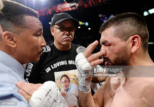 Alfredo Angulo has words with referee Tony Weeks as trainer Virgil Hunter looks on after Weeks stopped the fight in the 10th round of the nontitle...
