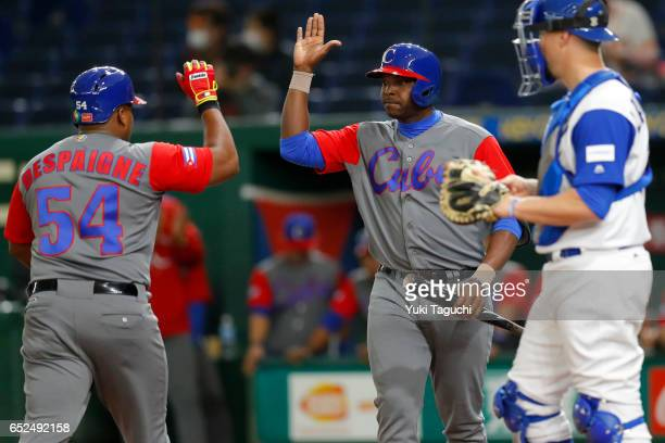Alfredo Despaigne of Team Cuba is greeted by teammate Willian Saavedra after hitting a solo home run in the second inning during Game 1 of Pool E...