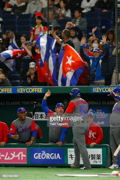 Alfredo Despaigne of Team Cuba is greeted in the dugout after hitting a solo home run in the second inning during Game 1 of Pool E against Team...