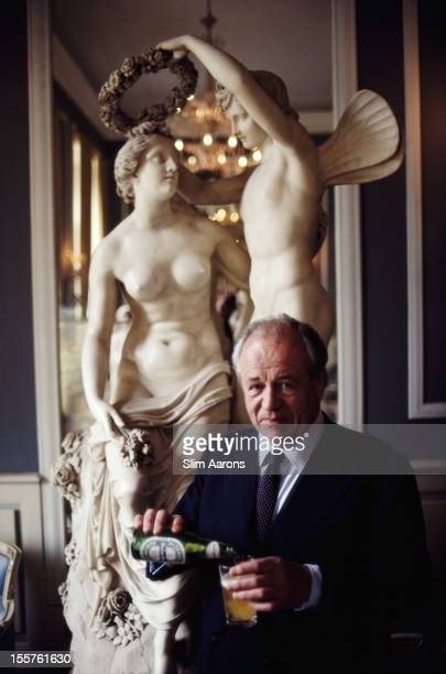 Alfredo Heineken poses by a sculpture while pouring a glass of Heineken beer from a bottle at the Villa d'Este on Lake Como at Tivoli near Rome Italy...