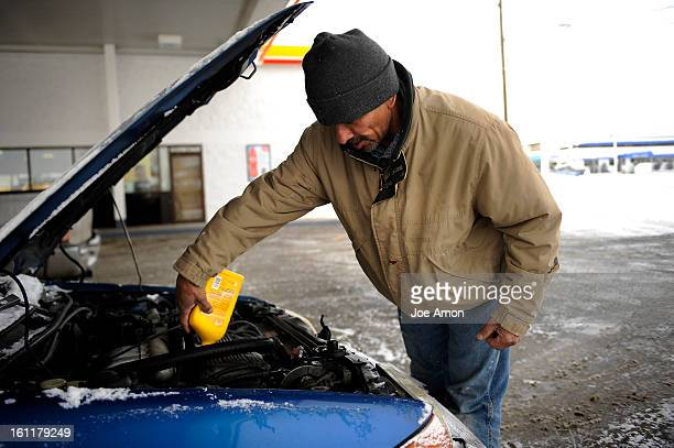 Alfredo Tejeda of Wheat Ridge fills the oil in his car at the pump in the brutal cold Tuesday morning on the 1st day of February. Joe Amon, The...