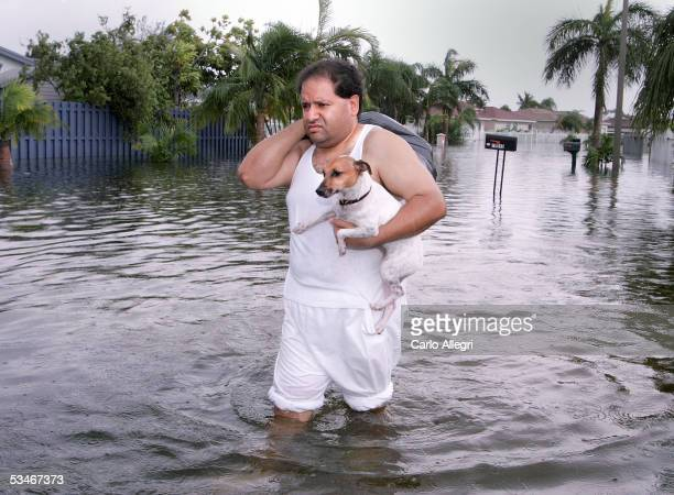Alfredo Velasquez leaves his home with a bag of clothes and his dog Jasmin under his arm after Hurricane Katrina dumped as much as 15 inches of rain...