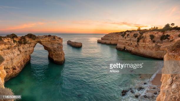 algarve beach at sunset. loving moment under natural arch carved in stone is a tourist attraction of the south coast of portugal. panoramic view from the cliff. - albufeira stock pictures, royalty-free photos & images