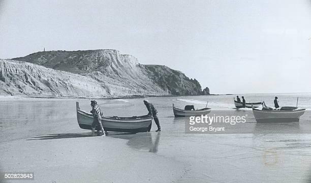 Algarve coast fishermen haul their boats ashore on a beach near Sagres