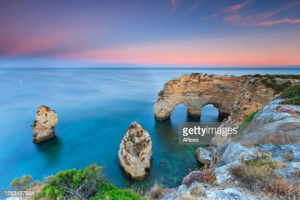 algarve in portugal and its amazing beaches, is a summer holiday destination for many tourists in europe. landscape with cliffs on the coast at colorful sunset. pure nature, blue sea, sand. - traditionally portuguese stock pictures, royalty-free photos & images