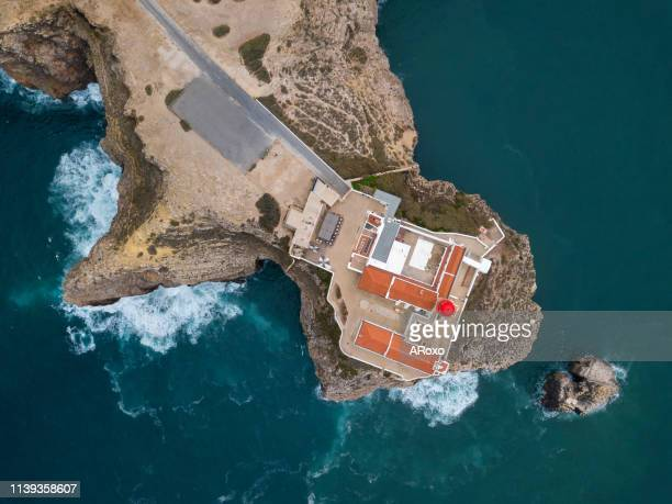 algarve seascape. aerial drone panoramic view of the lighthouse and cliffs at cape st. vincent at sunset. - faro city portugal fotografías e imágenes de stock