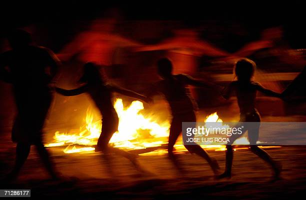 People dance around a bonfire 24 June 2006 during the traditional San Juan's night in a beach of Algeciras southern Spain Fires are lit throughout...
