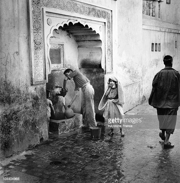 Algeria a young boy fills his jug at a street fountain in Algiers casbah