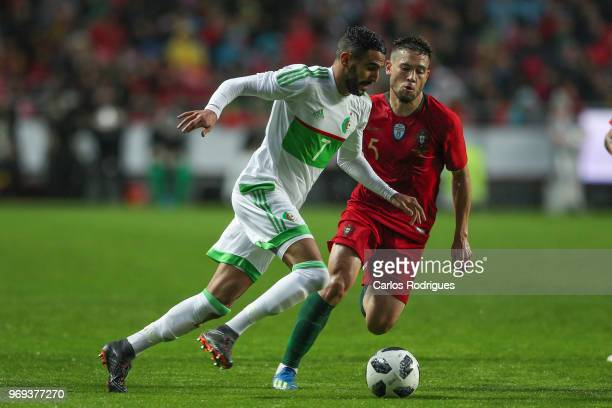Algeria and Leicester City FC forward Riyad Mahrez vies with Portugal and Borussia Dortmund defender Raphael Guerreiro for the ball possession during...