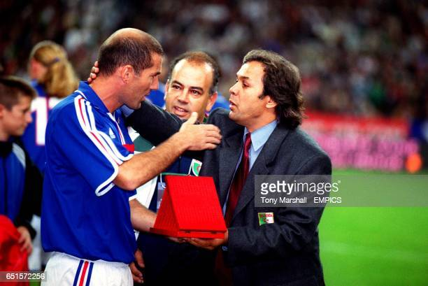 Algeria Coach Rabah Madjer presents a souvenir to France's Zinedine Zidane a Frenchman of Algerian parentage