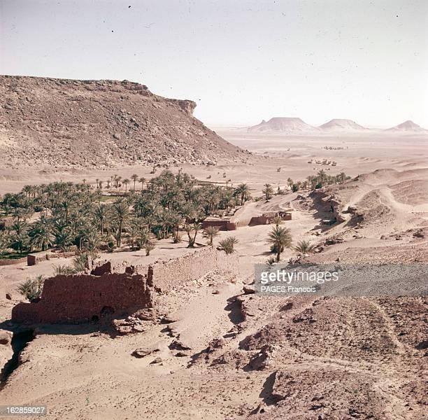 Algeria En Algérie une vue aérienne sur un village dans une oasis avec sa végétation au milieu du désert montagneux
