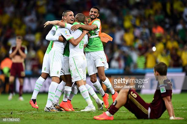 Algeria players celebrate qualifying for the knock out stage while Alexander Kokorin of Russia show his dejection after the 11 draw in the 2014 FIFA...
