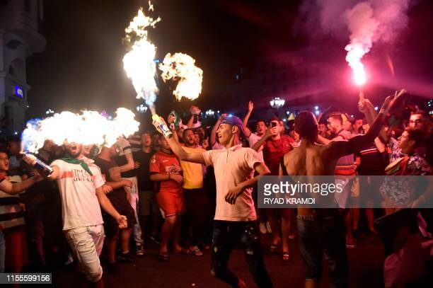 Algeria supporters celebrate after Algeria won the 2019 Africa Cup of Nations semifinal football match against Nigeria on the Grande Poste place in...