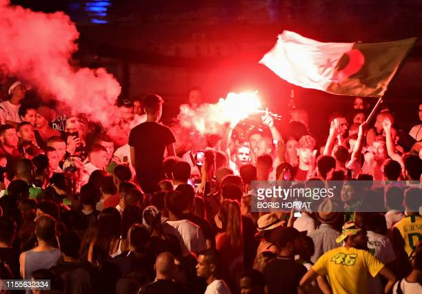 TOPSHOT Algeria supporters celebrate after Algeria won the 2019 Africa Cup of Nations semifinal football match against Nigeria at the old harbour in...